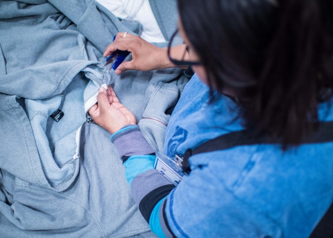 An employee at JC Industries trimming threads on the Backyard Project full-zip hoodie as the final stage in the production process. JC Industries, based in Los Angeles, started in the 1970s making custom trims and has expanded its operations over the years to offer vertical manufacturing. Photo credit: Bright Black