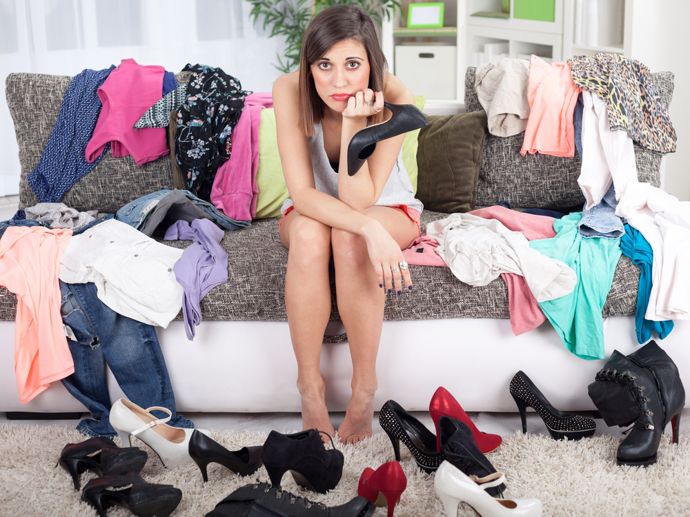 girl surrounded by pile of clothing and shoes looking frustrated