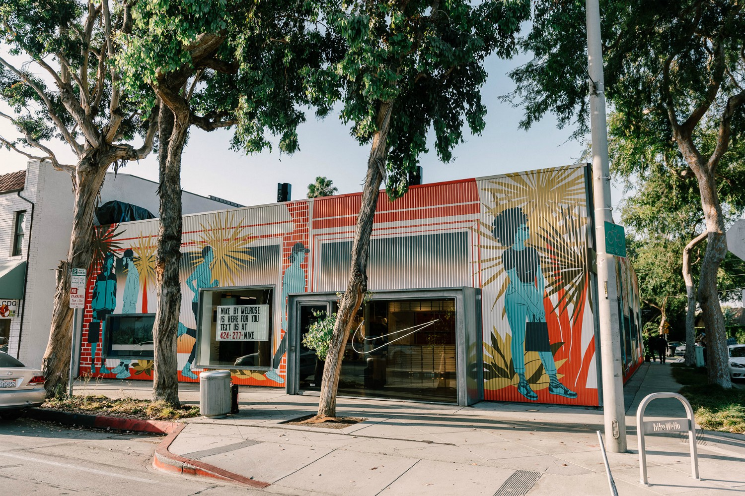 "The store's façade showcases Angelenos shopping and getting after sport against the backdrop of a classic SoCal sunset. Los Angeles native Bijou Karman, the artist and illustrator who designed the mural that she calls ""Sunsets on Melrose,"" says she intended for it to be a re-imagined walkthrough of a typical LA day."