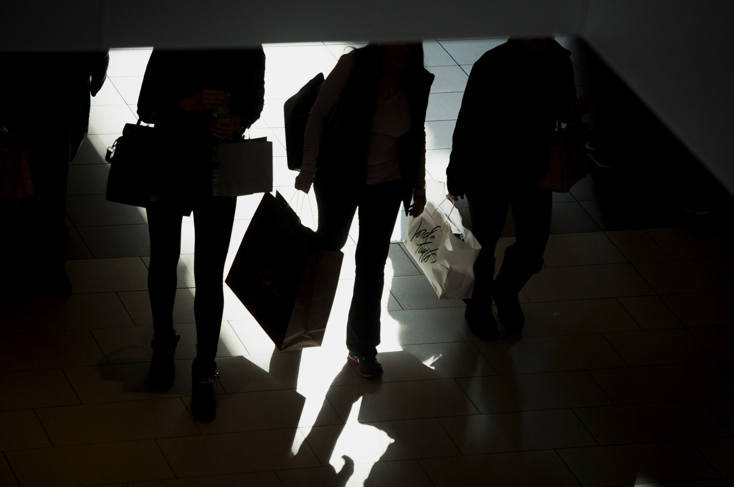 silhouettes of shoppers seen carrying bags
