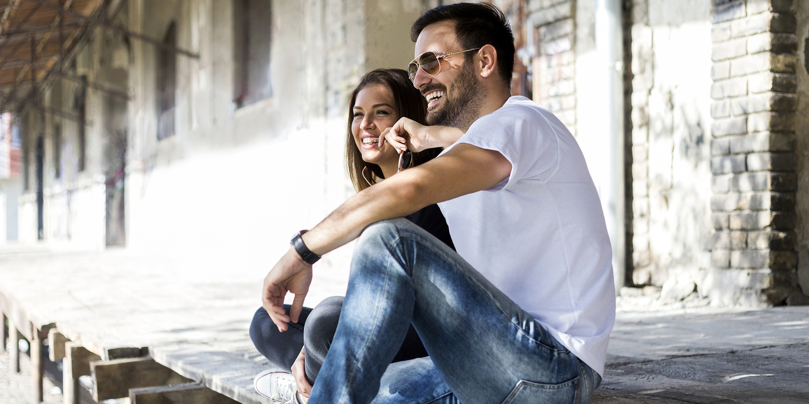 Casual happy couple dating and sitting outdoor