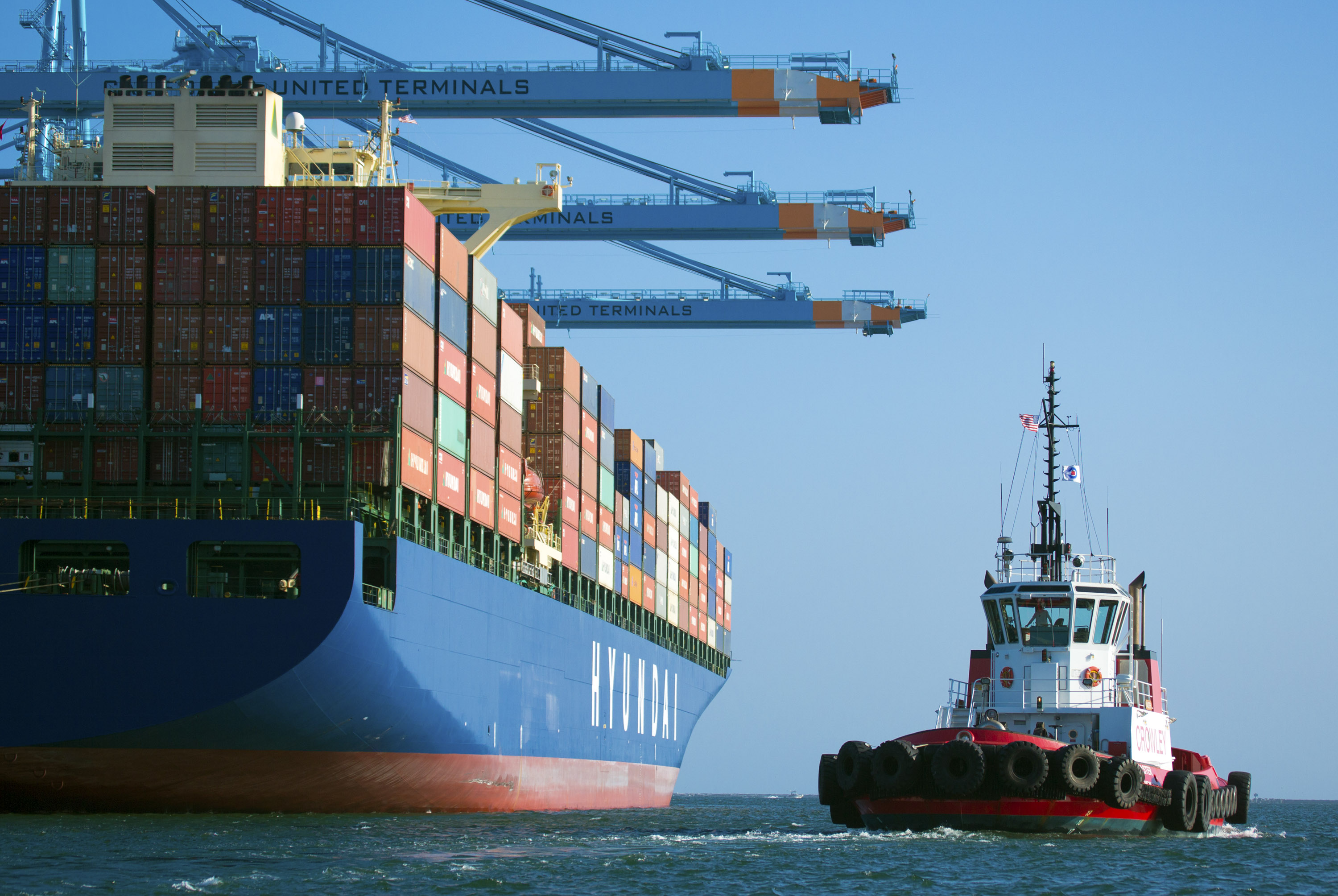 A tug boat moves into position with a Hyundai container ship in the Port of Los Angeles