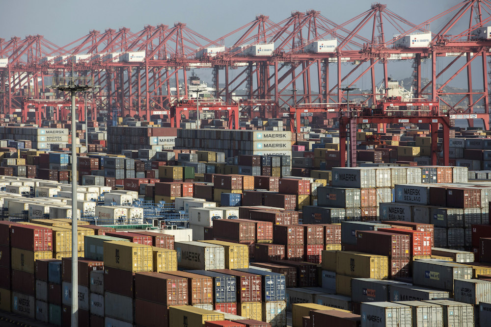 Containers sit stacked next to gantry cranes at the Yangshan Deep Water Port in Shanghai, China