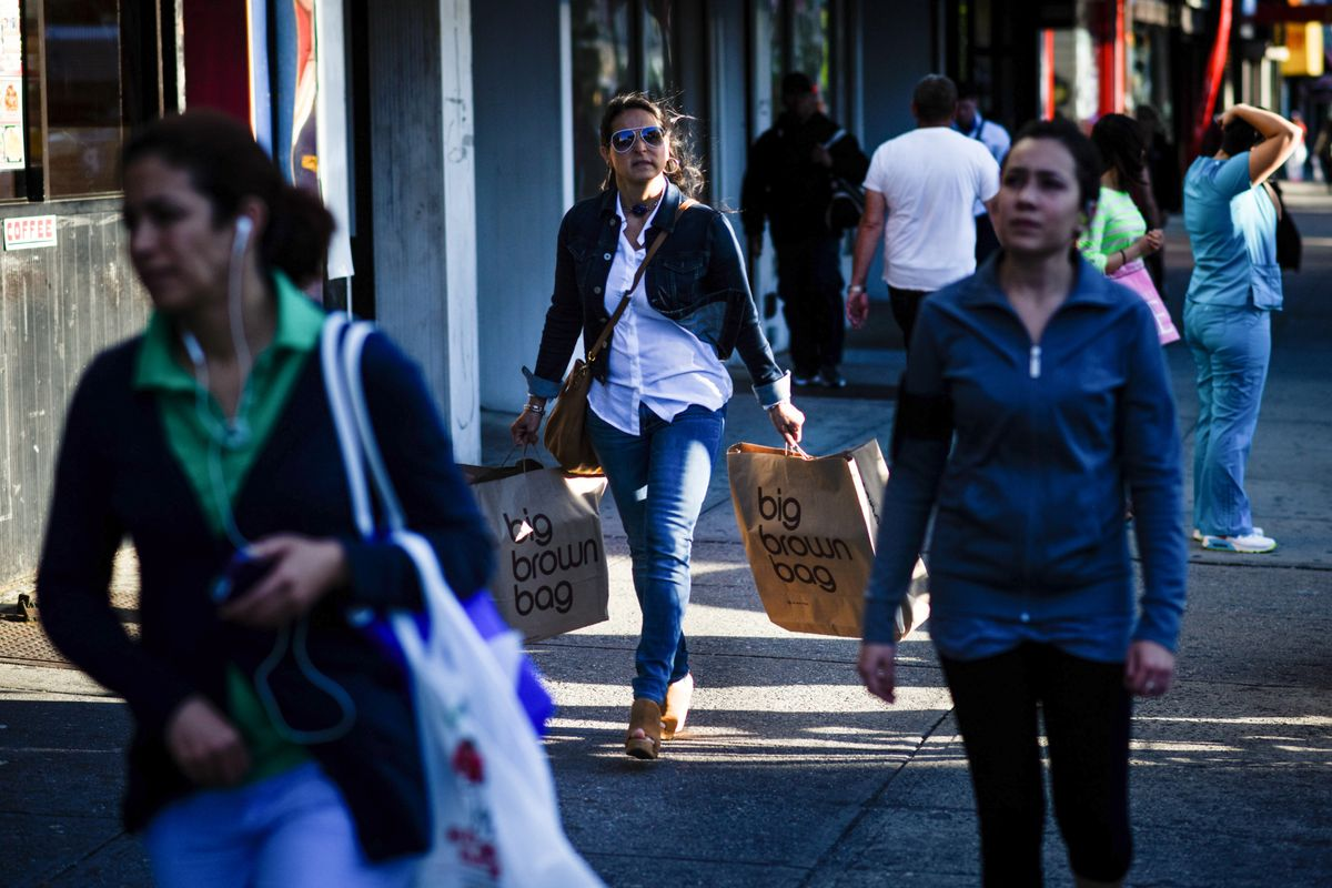 A shopper carries Bloomingdale's Inc. bags while walking on Steinway Street in the Queens borough of New York, U.S.