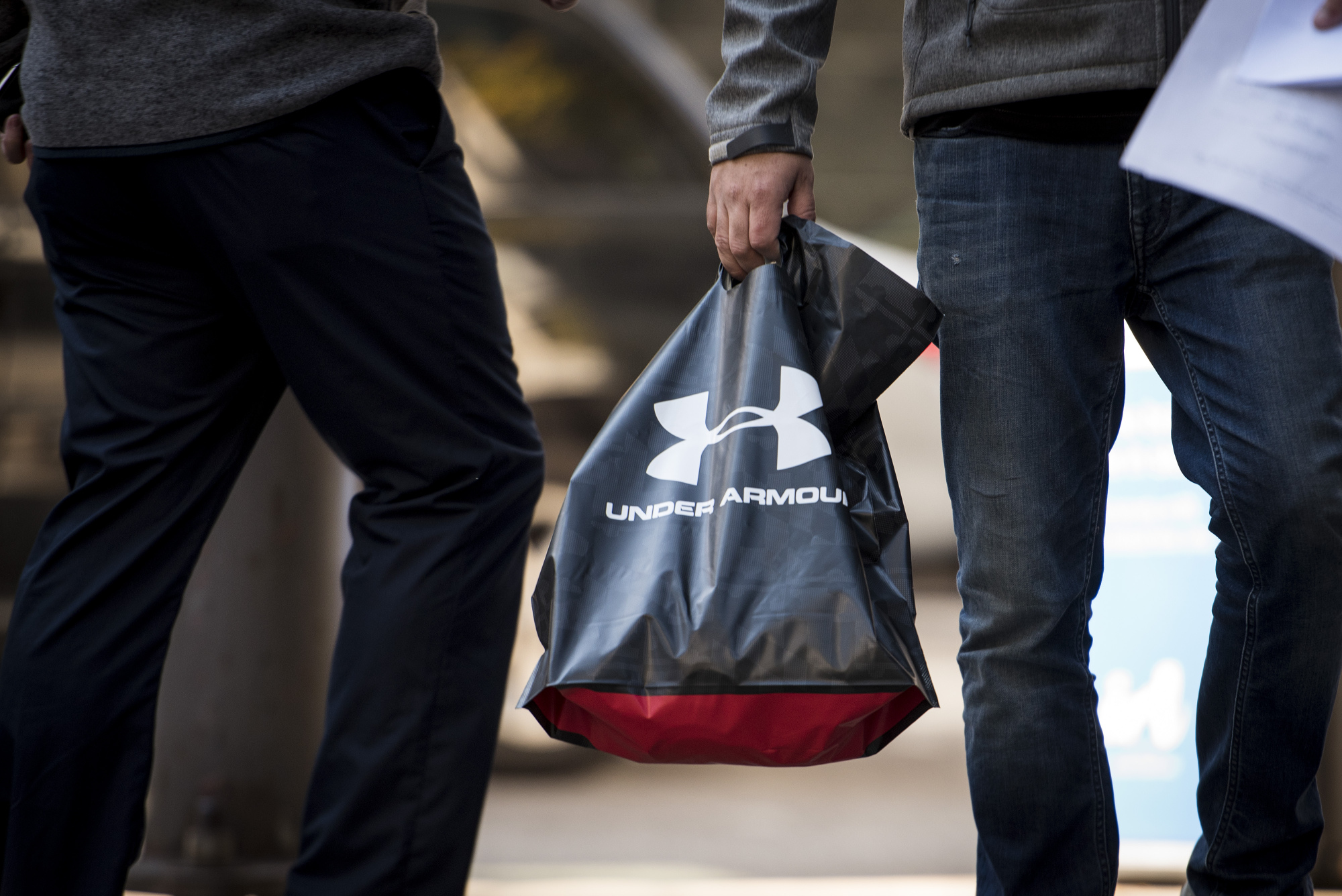 A pedestrian carries an Under Armour Inc. shopping bag in downtown Chicago, Illinois.
