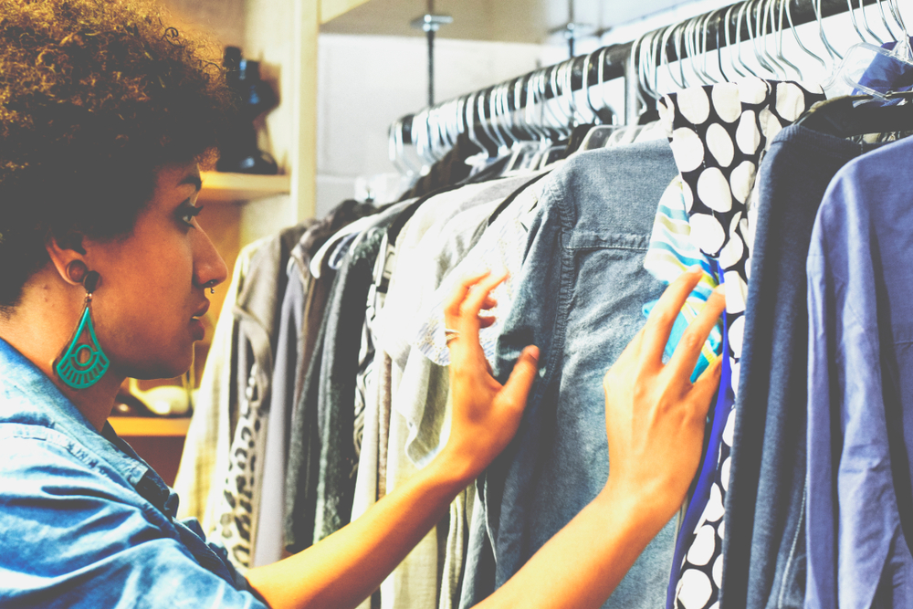 girl perusing rack of thrift clothing