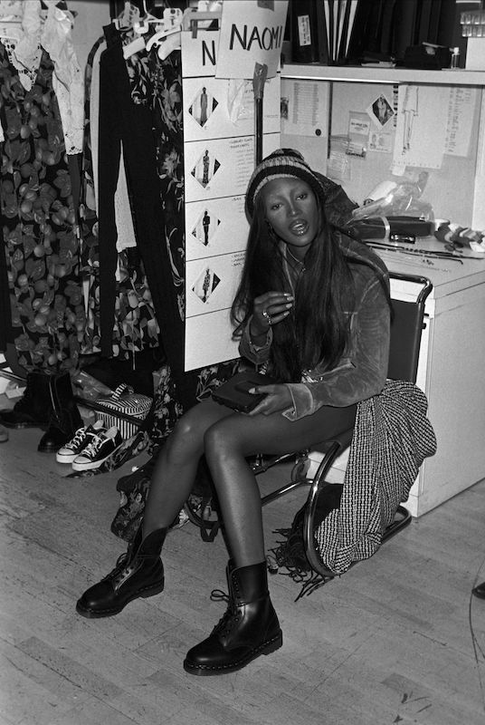 Model Naomi Campbell seated backstage.