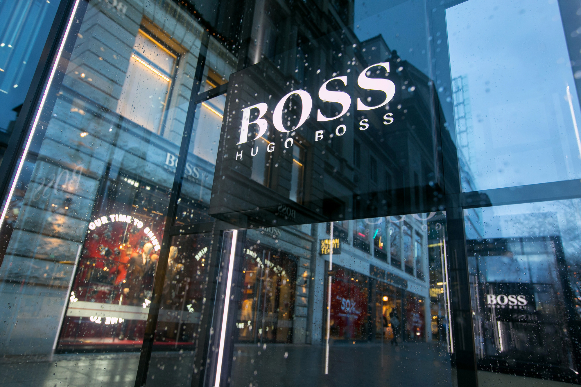 A logo stands outside a Hugo Boss AG luxury clothing store in Berlin, Germany.