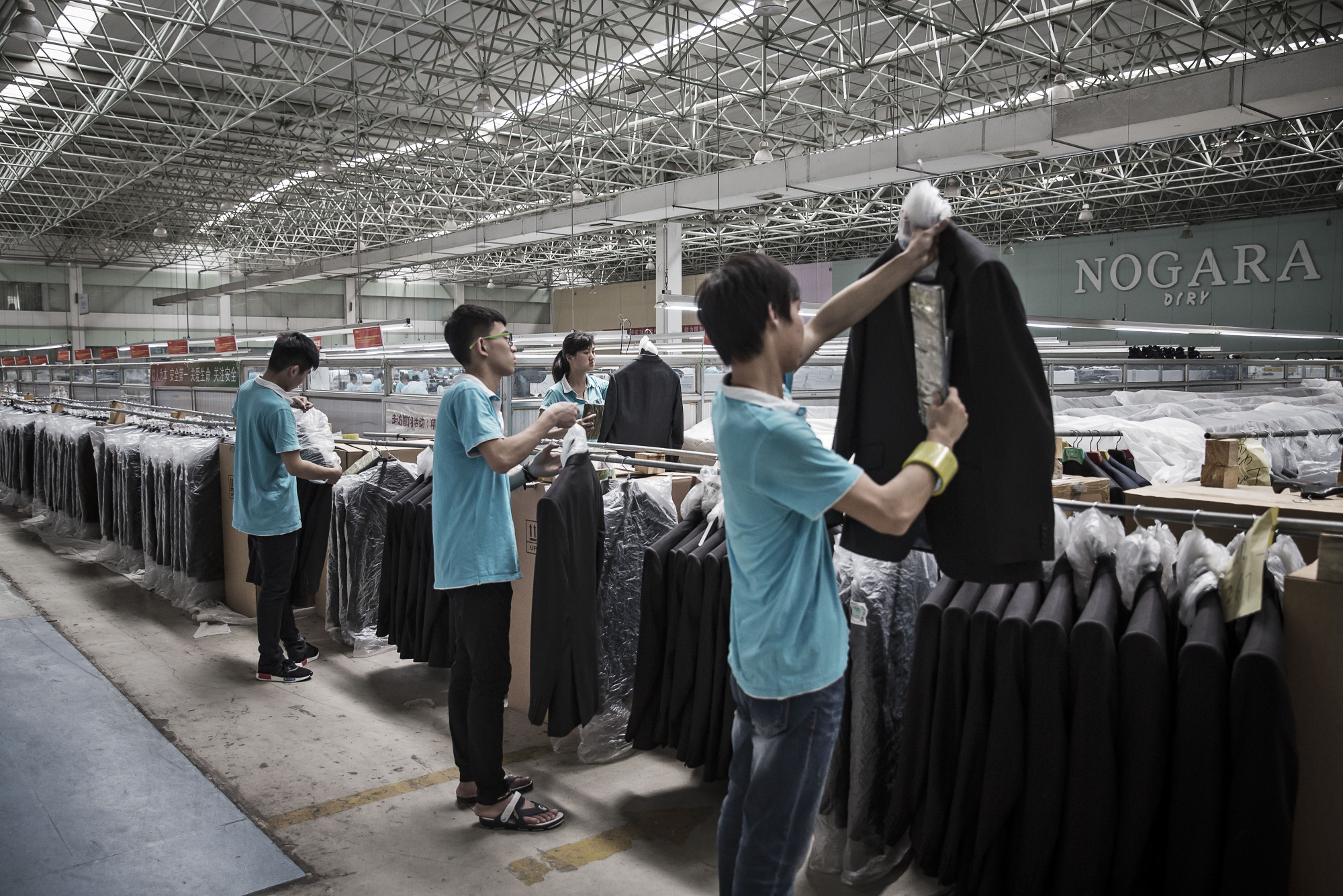 Employees place suit jackets in plastic covers at a Ruyi factory in China