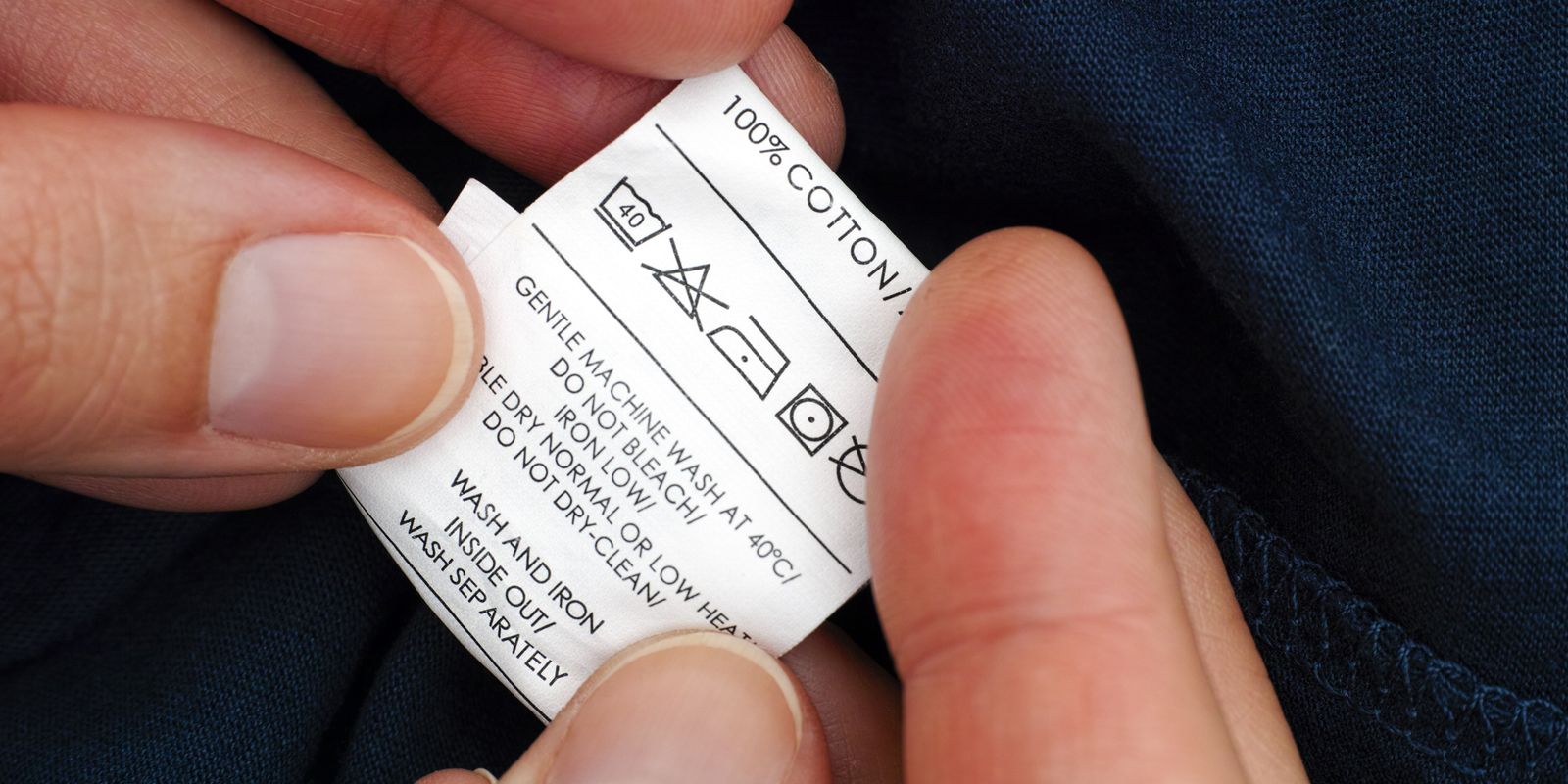 Woman hands holding clothes label with cleaning instructions