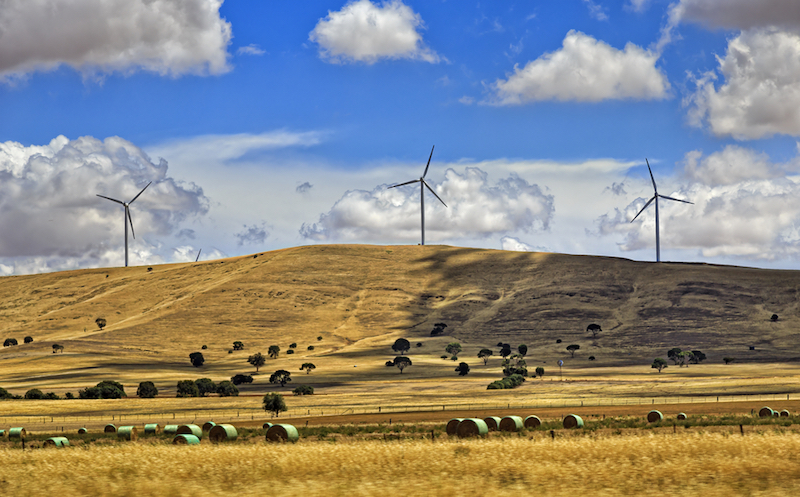 Rural region with cultivated farms and haystacks providing grounds for renewable energy