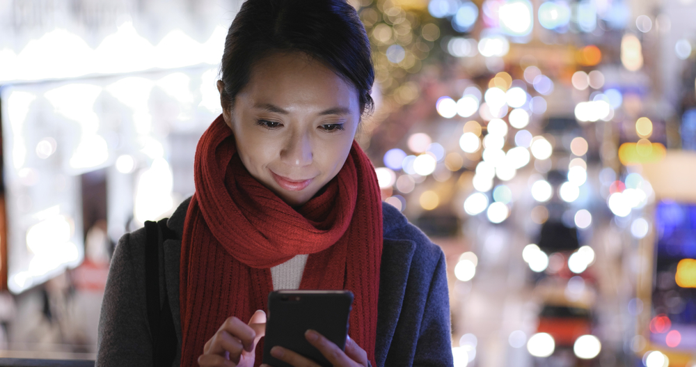 Woman use of mobile phone in city over traffic background