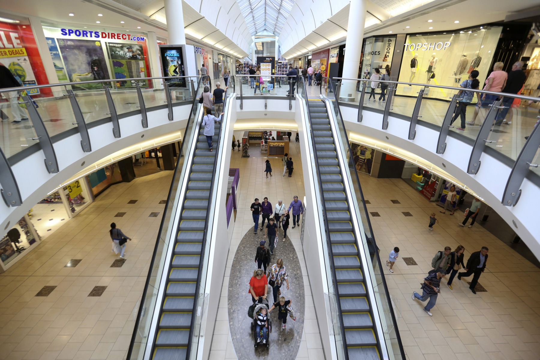 Shoppers pass through Lakeside shopping centre, operated by Intu Properties Plc., in Thurrock, U.K