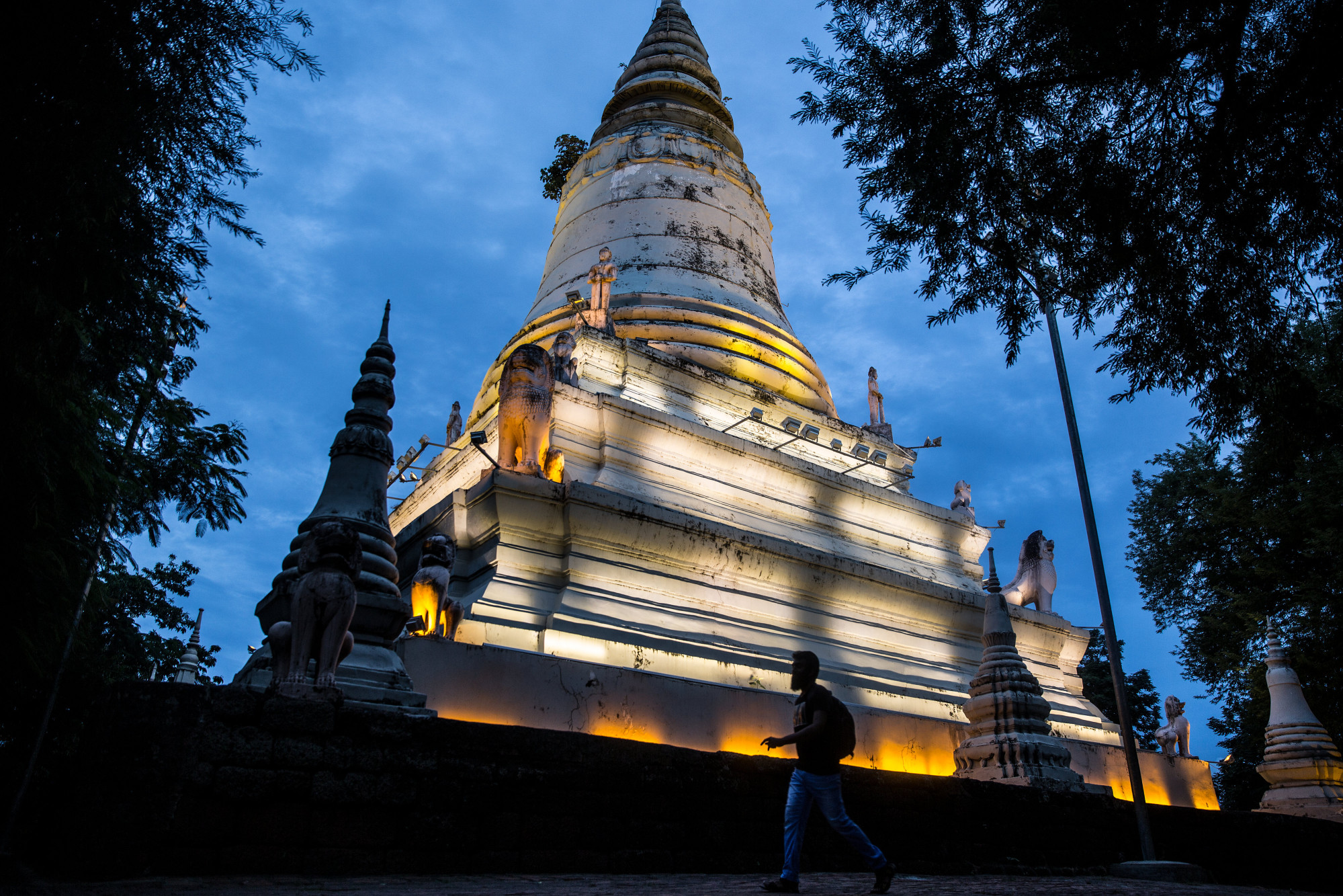 A pedestrian walks past the Wat Phnom temple illuminated at dusk in Phnom Penh, Cambodia