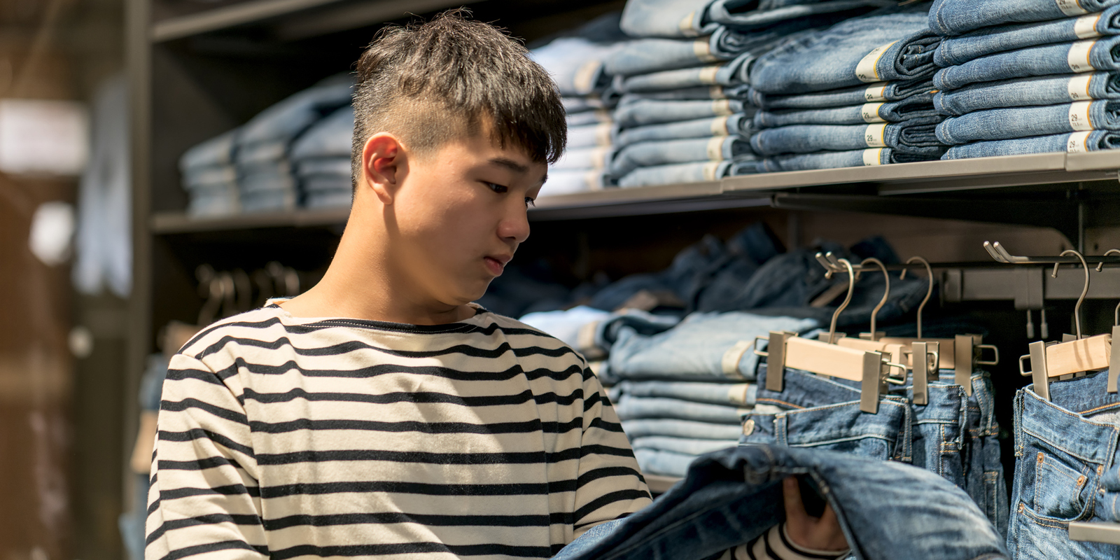 Teenage boy shopping for clothes in a discount store.