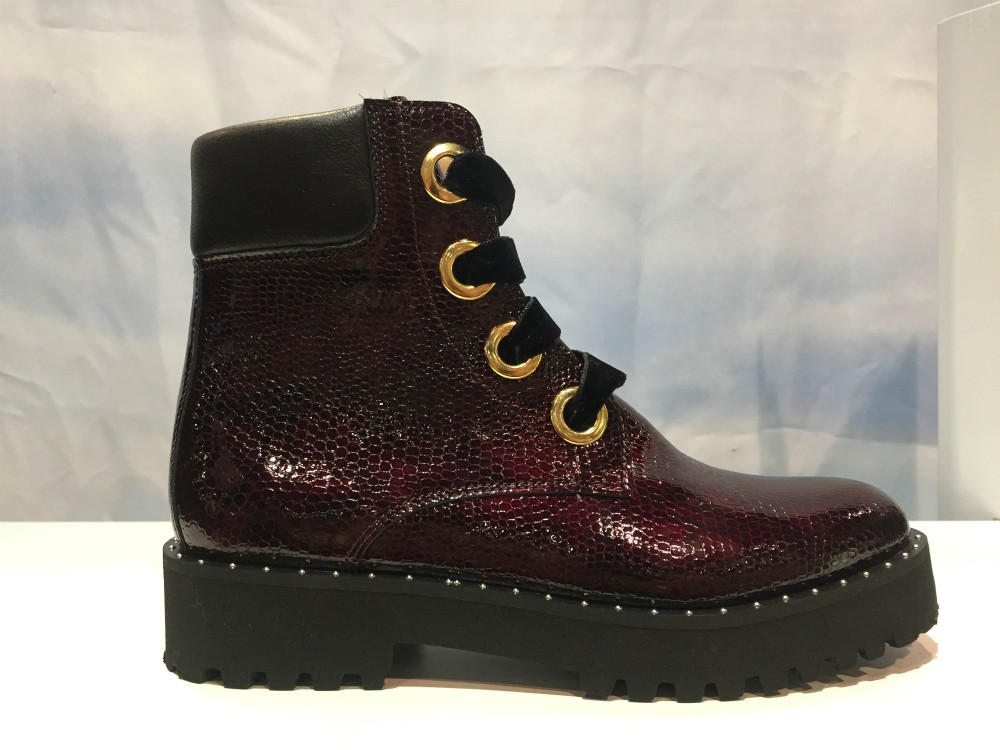 Andre Assous' lace-up combat boot featured an all-over, snakeskin-textured patent in rich burgundy