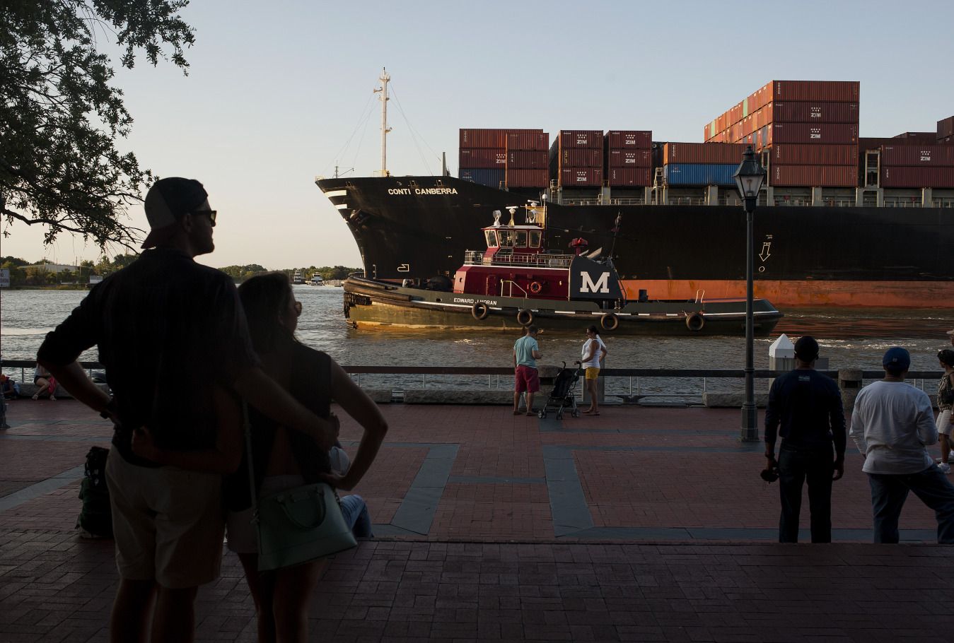 Pedestrians watch from River Street as a cargo ship and a tug boat travel into the Port of Savannah on the Savannah River in Savannah, Georgia, U.S.