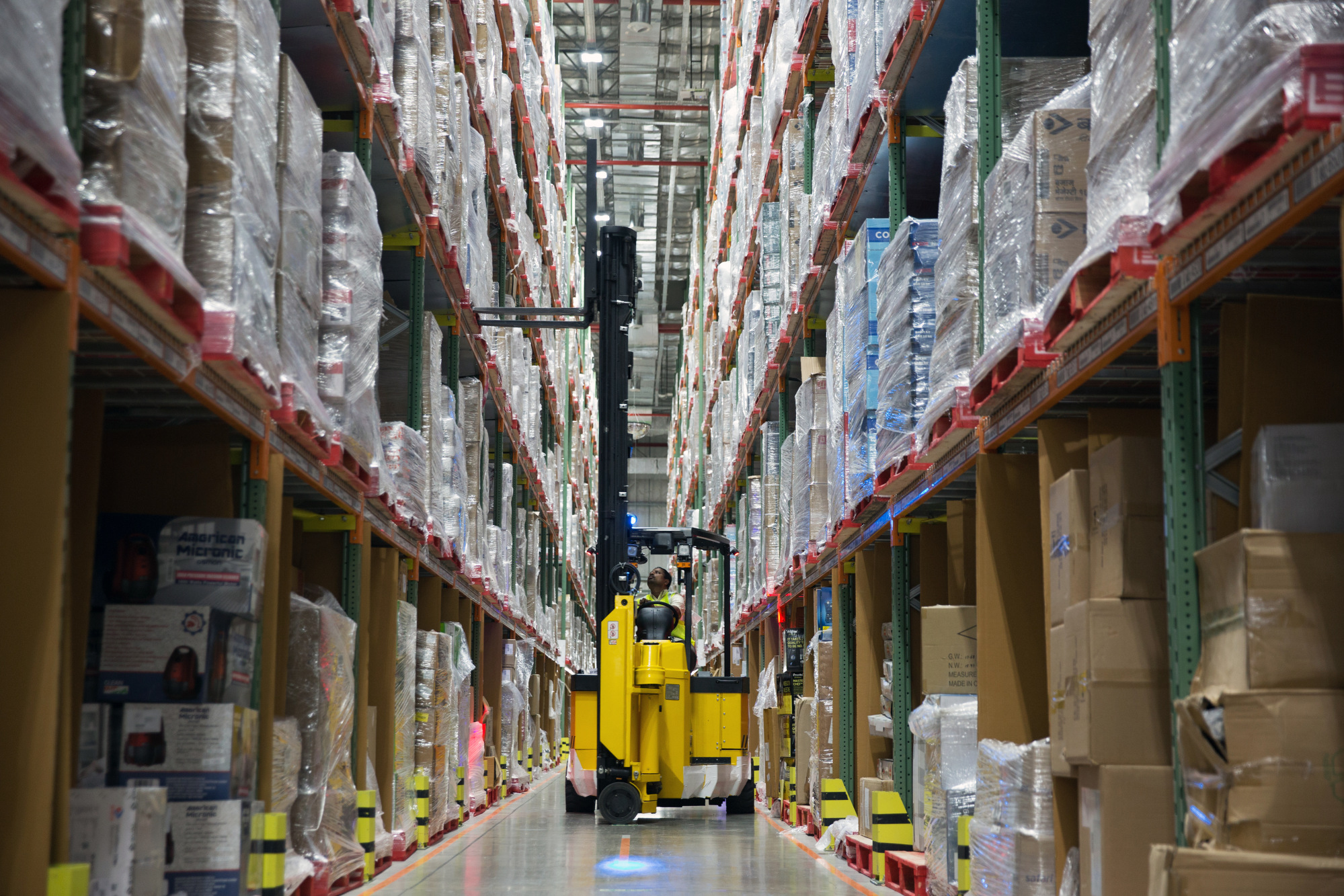 A worker uses a forklift to remove a pallet of goods from a storage rack in an aisle at the Amazon Inc. fulfillment center in Bengaluru, India.