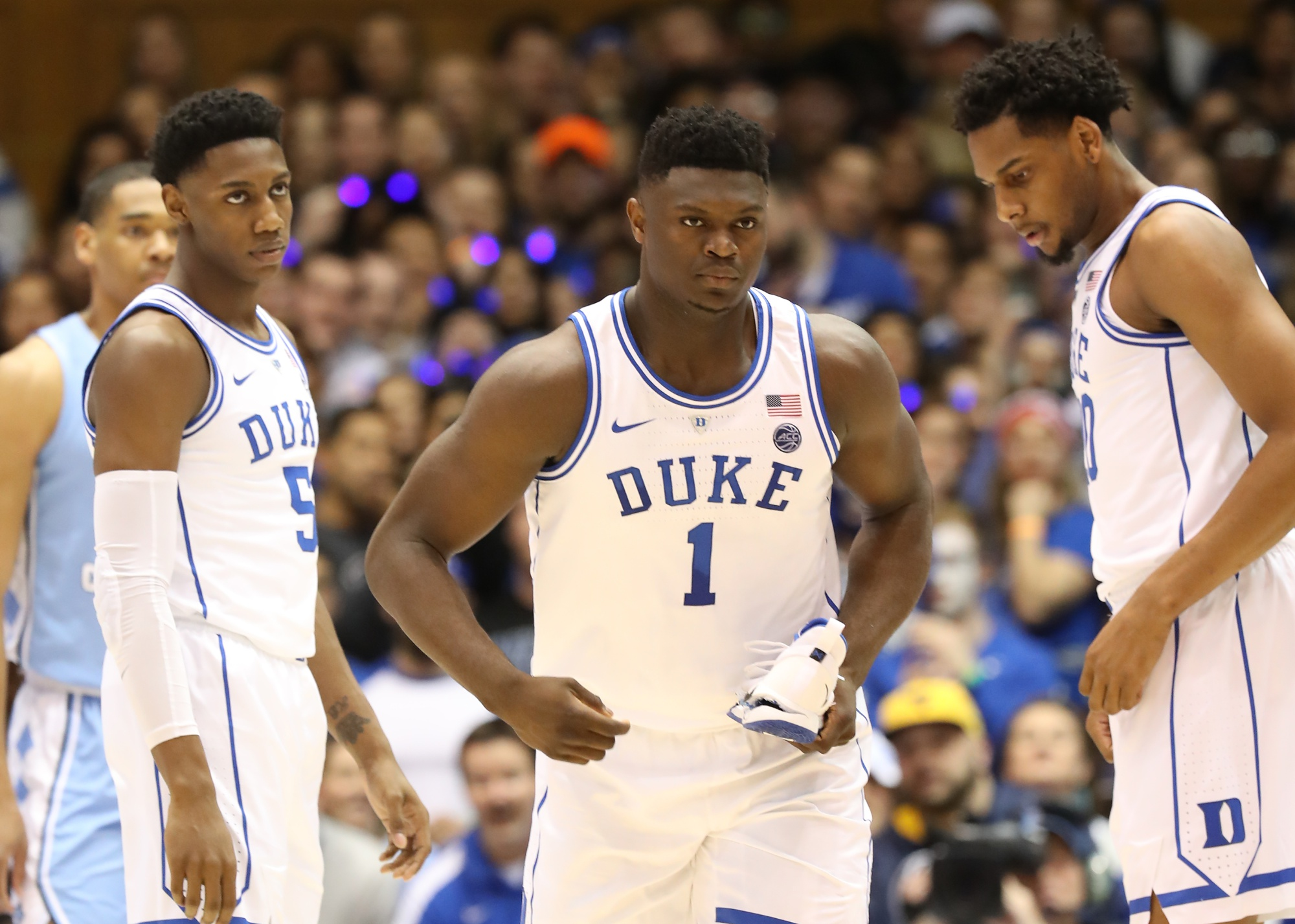Teammates RJ Barrett #5 and Marques Bolden #20 of the Duke Blue Devils watch as Zion Williamson #1 of the Duke Blue Devils reacts after falling as his shoe breaks against Luke Maye #32 of the North Carolina Tar Heels during their game at Cameron Indoor Stadium on February 20, 2019 in Durham, North Carolina.