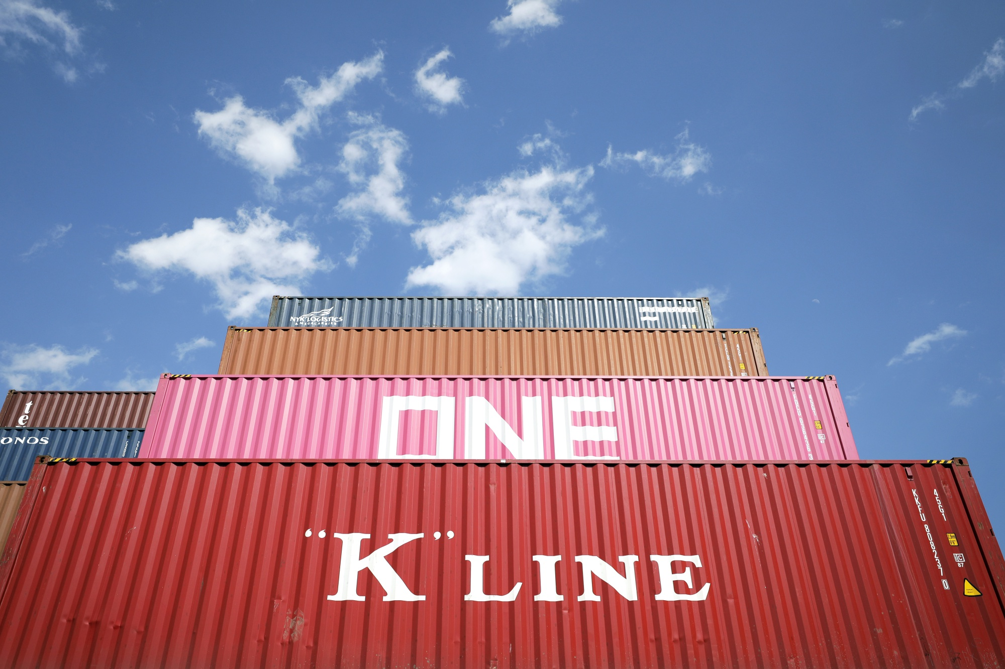 Shipping containers sit stacked at a terminal in Tokyo, Japan