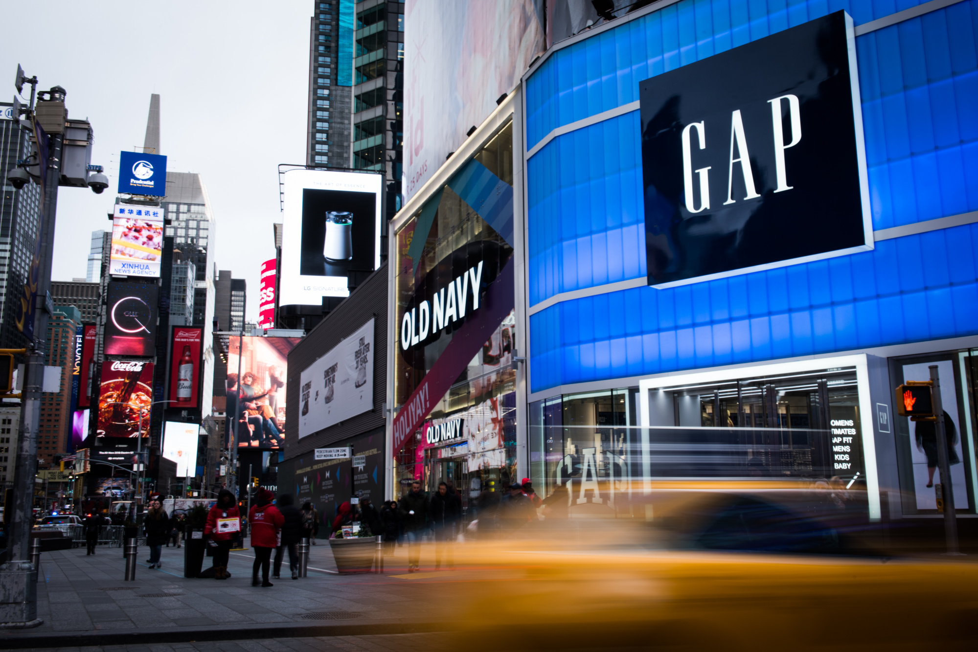 Pedestrians pass in front of Gap Inc. and Old Navy Inc. stores in the Times Square area of New York, U.S., on Wednesday, Dec. 13, 2017.