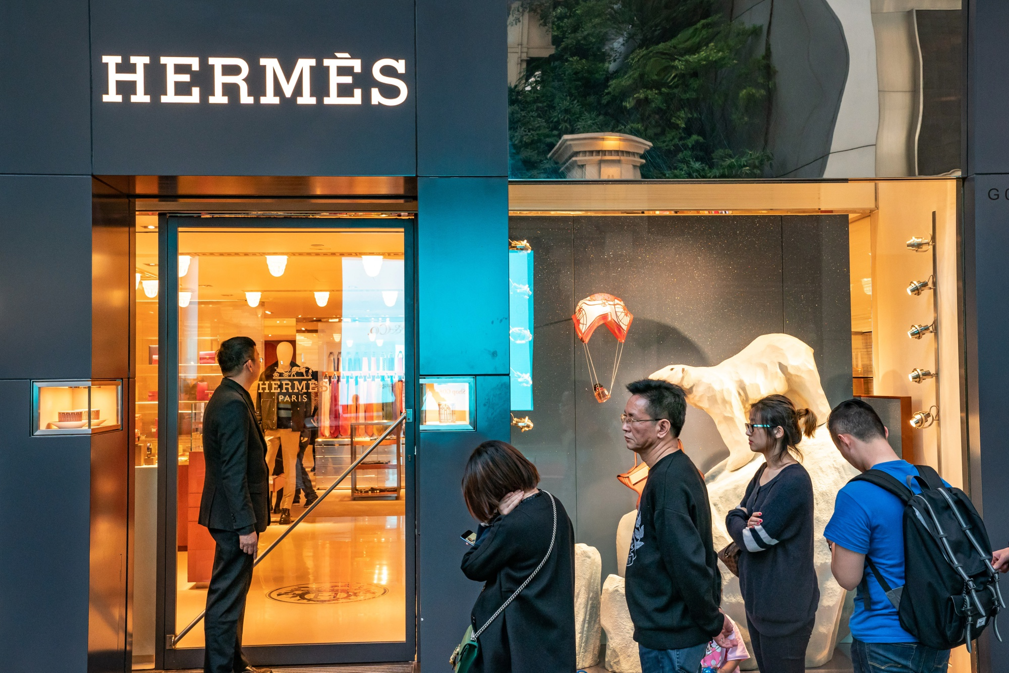 Shoppers wait in line outside a Hermes International SCA store on Canton Road in the Tsim Sha Tsui district of Hong Kong, China.