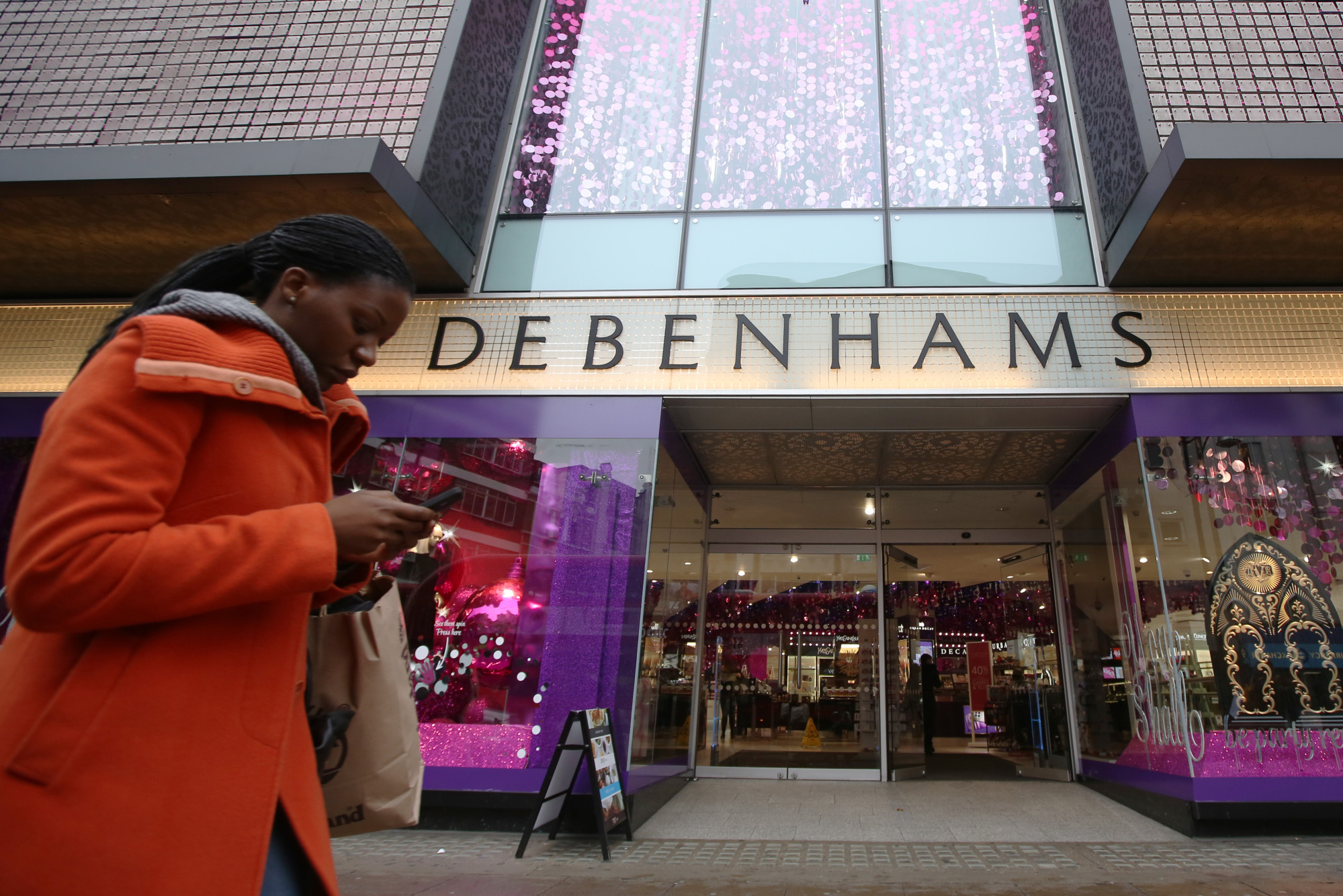 A shopper uses a mobile device as she walks past the entrance to a Debenhams Plc department store in London, U.K