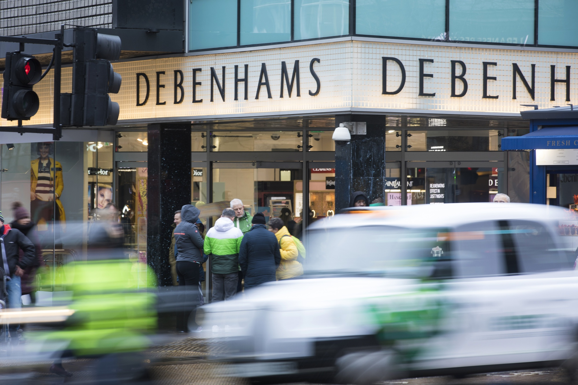Traffic moves along the road outside a Debenhams Plc department store on Oxford Street in central London, U.K.
