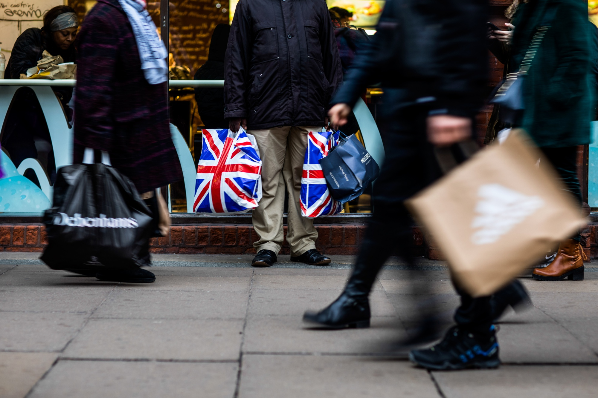 A pedestrian holds shopping bags branded with the Union Flag, also know as Union Jack, on Oxford Street in central London, U.K., on Tuesday, Dec. 4, 2018.