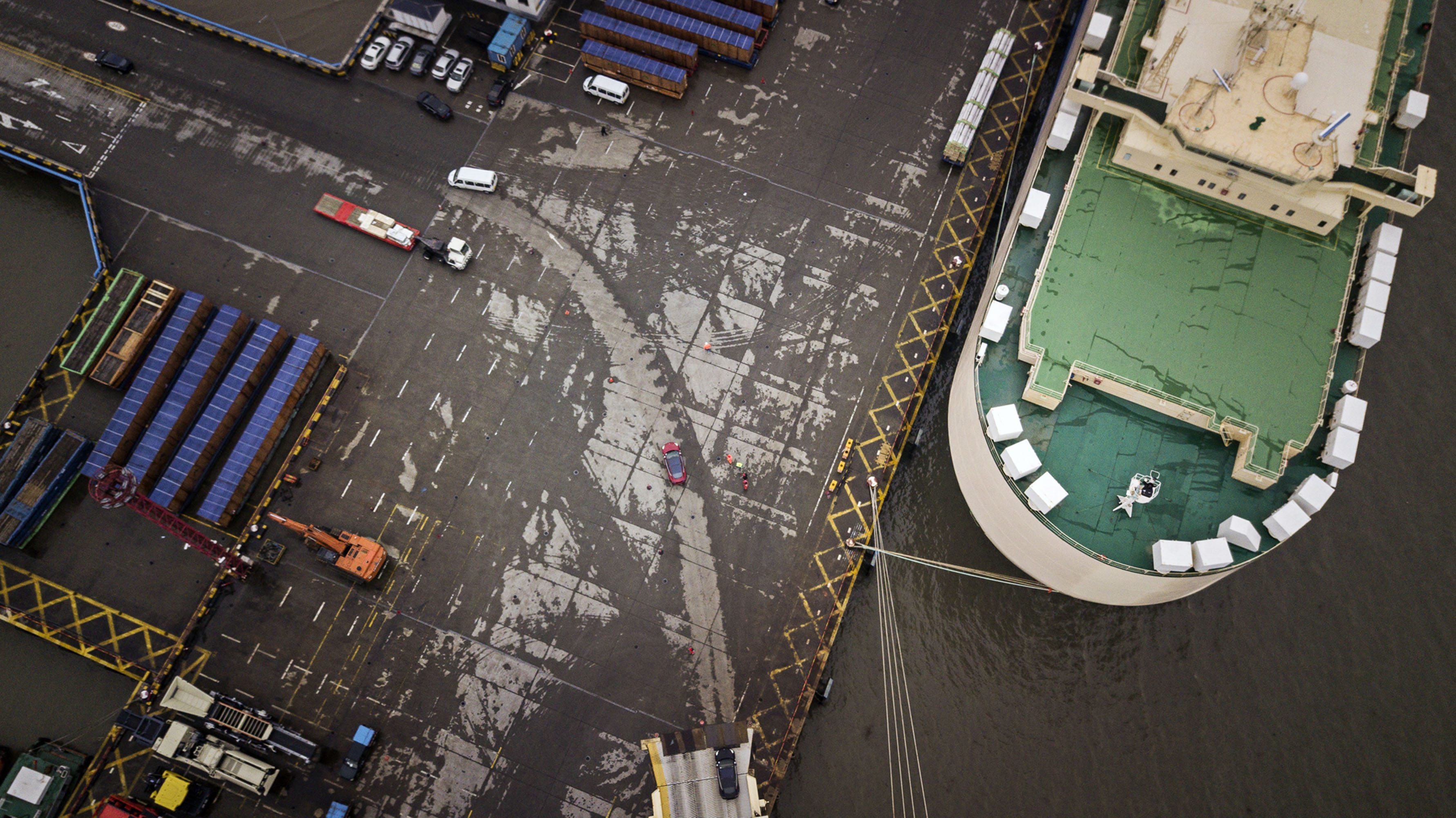A Tesla Inc. Model 3 electric vehicle, center, travels through a port after being driven off the Morning Cindy vehicle carrier in this aerial photograph taken in Shanghai, China.