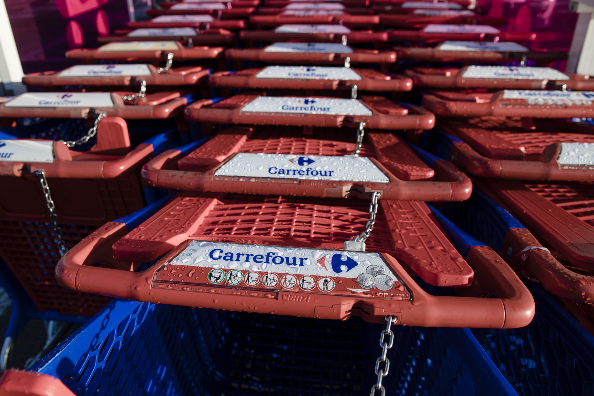 Locked shopping carts stand in a customer collection bay outside a Carrefour SA supermarket in the Rosny-sous-bois district of Paris, France.