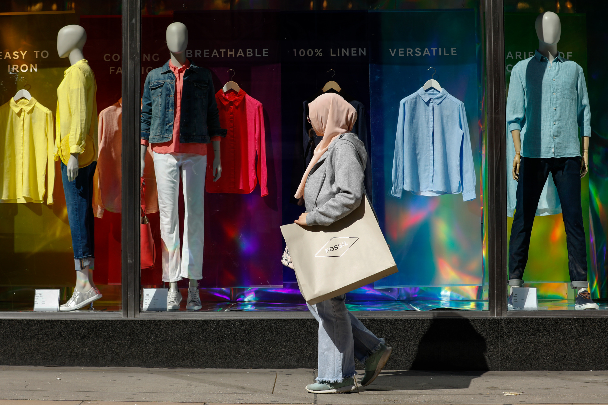 A woman wearing a headscarf carries a shopping bag past a Marks & Spencer Group Plc store on Oxford Street in central London, U.K., on Tuesday, April 17, 2018.