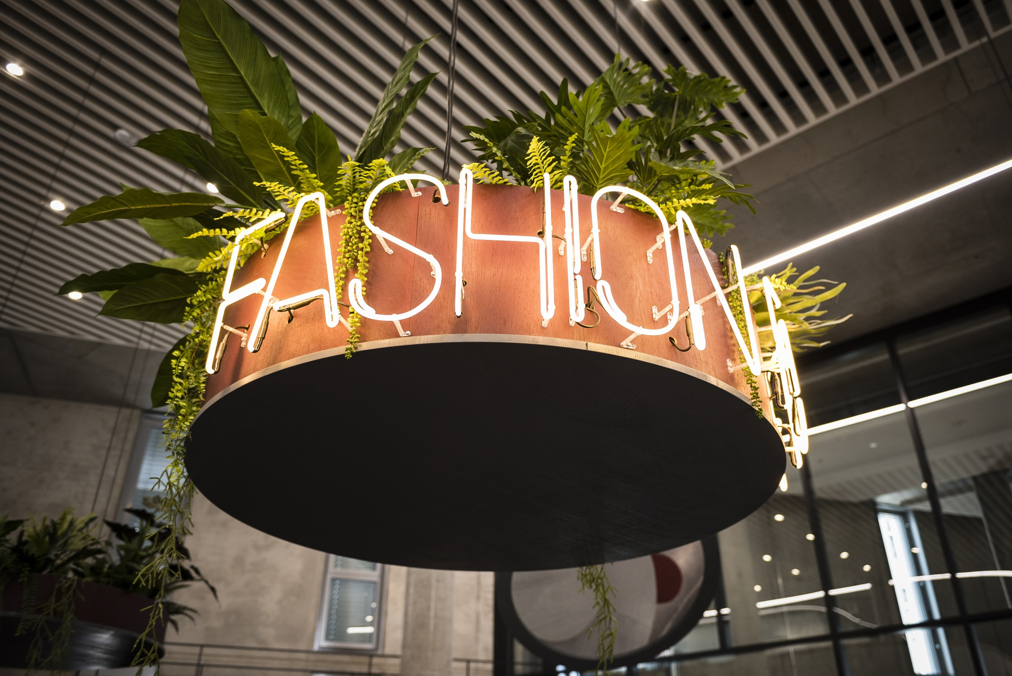 Neon lettering spells out fashion on a hanging plant basket in a rest area at Zalando SE's new campus headquarters in Berlin, Germany.
