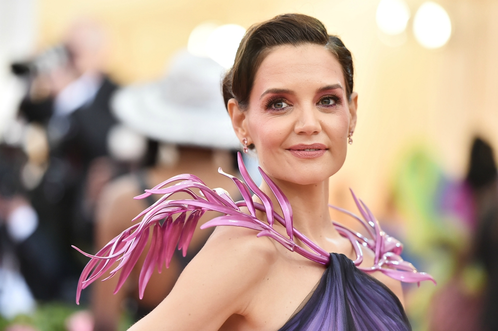 Katie Holmes wore a custom Zac Posen gown with a Zac Posen x GE Additive x Protolabs 3D printed palm leaf collar accessory. The pearlescent purple palm leaves are draped over the shoulders and attached to the gown at the neckline.