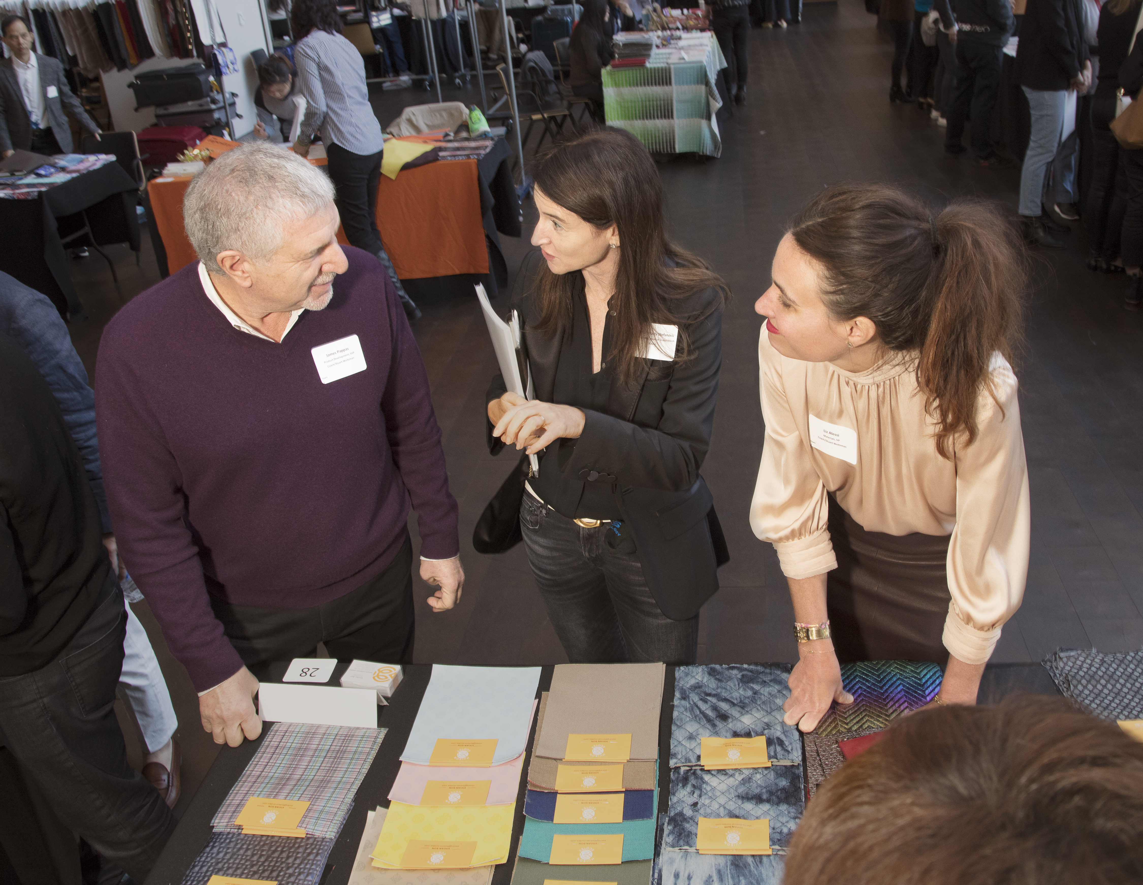James Pappas, senior vice president for product development at Coach, with team members at a vendor table.