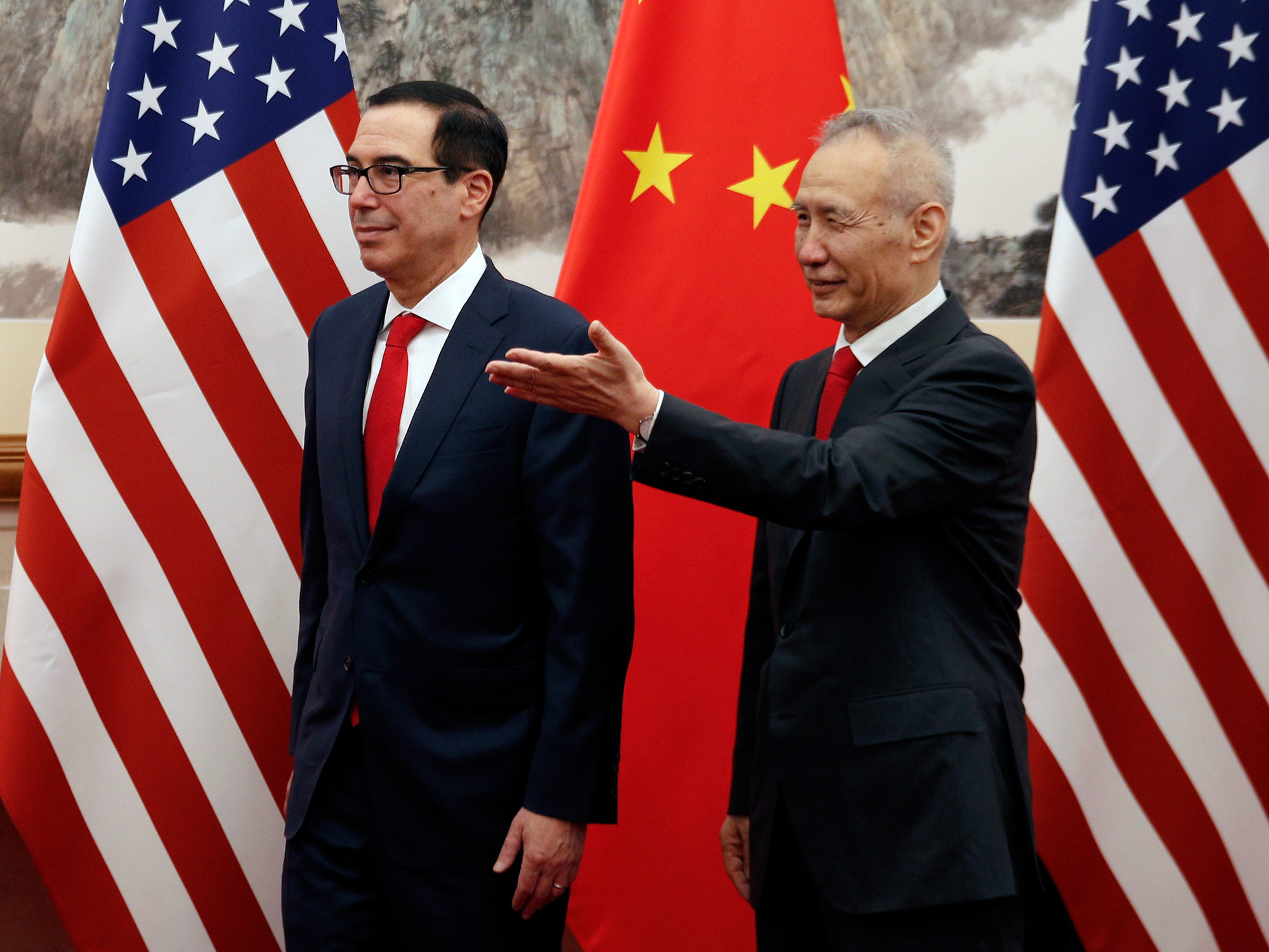 Chinese Vice Premier Liu He (R) shows the way to US Treasury Secretary Steven Mnuchin as they proceed for their meeting at the Diaoyutai State Guesthouse in Beijing on May 1, 2019.