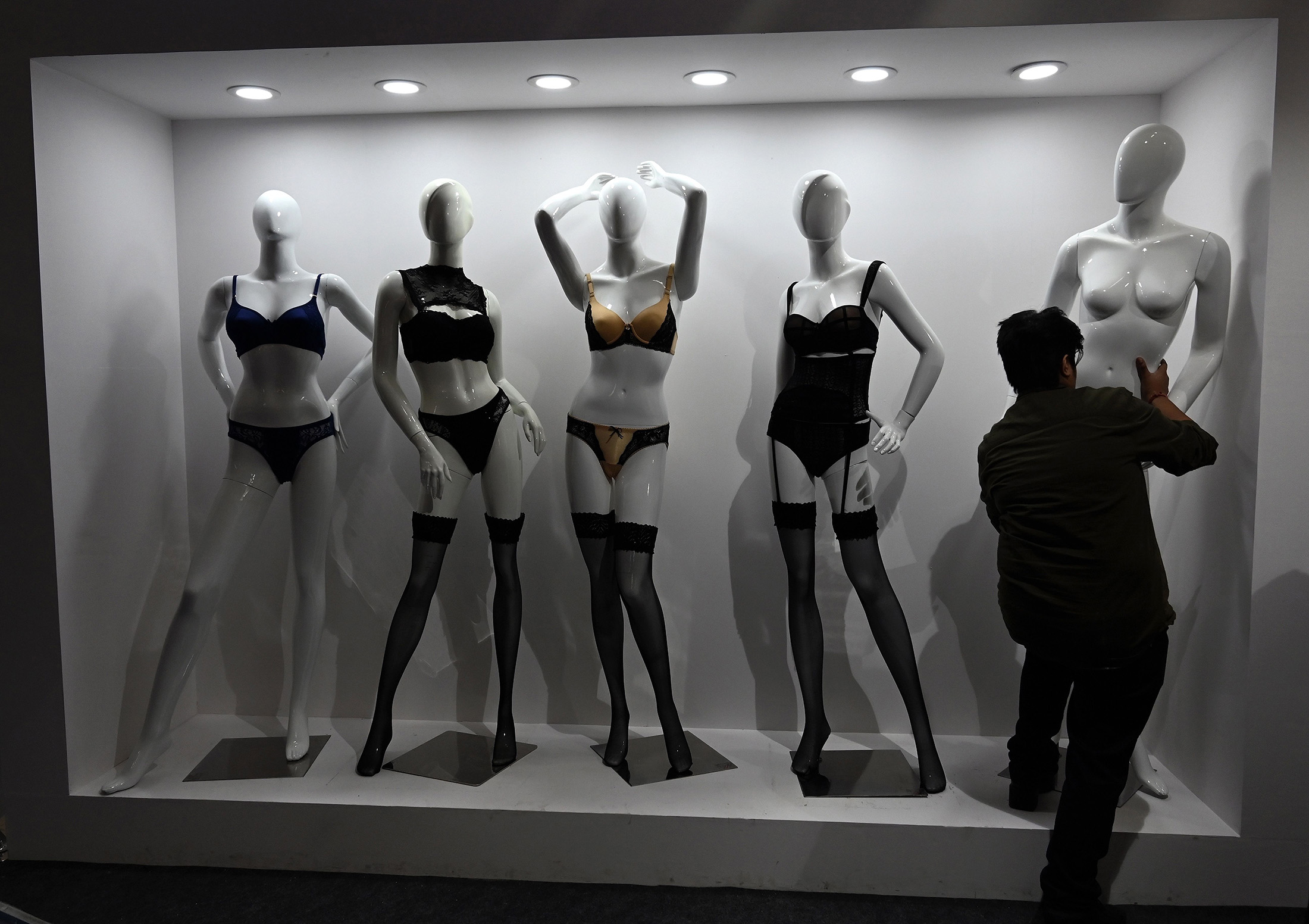 "An exhibitor dresses mannequins during Intimasia Expo-2019, an ""Intimate Wear Show"", in New Delhi on January 21, 2019. - Retailers from 84 neighboring cities are participating in the Intimasia Expo-2019, showcasing underwear, sleepwear, swimwear, and active clothing."