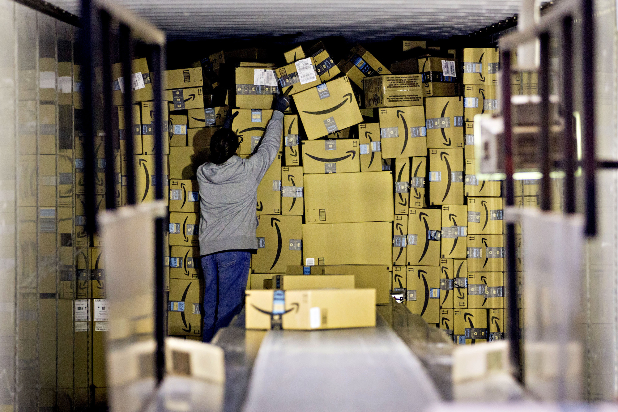 An employee unloads a truck load of Amazon.com Inc. packages at the United Parcel Service Inc. (UPS) Chicago Area Consolidation Hub in Hodgkins, Illinois, U.S.