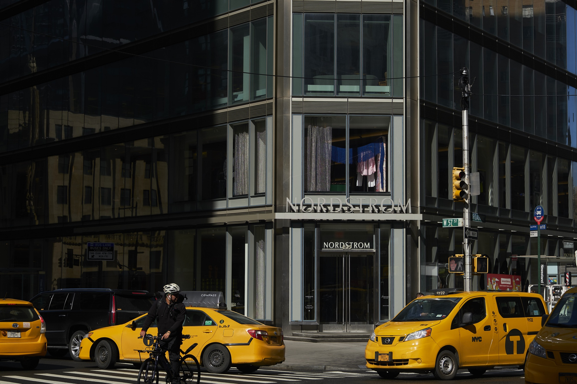Taxis pass in front of a Nordstrom Inc. Men's store in New York, U.S., on Thursday, Feb. 21, 2019.