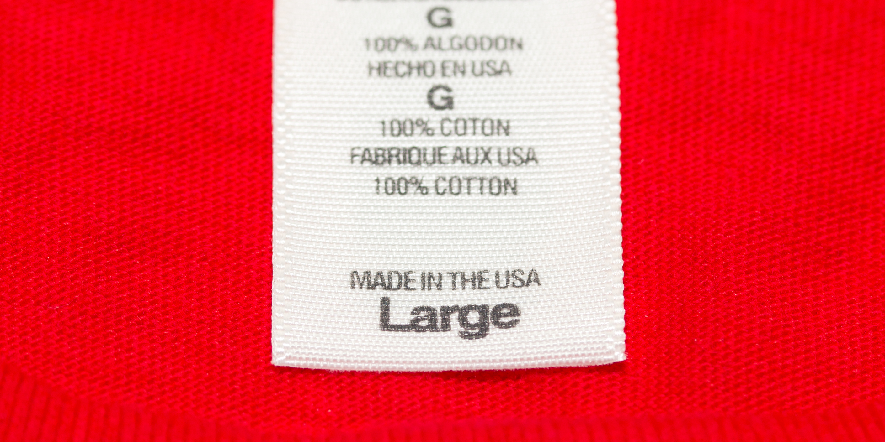 """Close up """"Made in the USA"""" clothes label on a large red t-shirt. Shot with macro lens."""