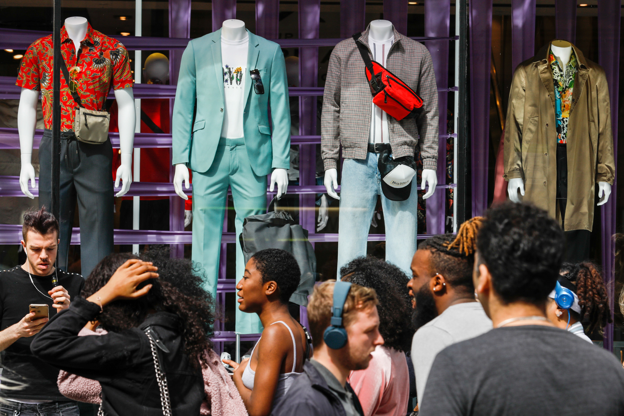 Shoppers pass TopShop retail store, operated by Arcadia Group Ltd., on Oxford Street in central London.