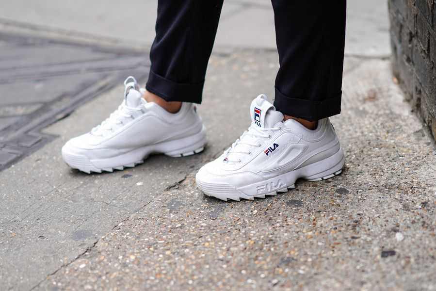 A guest wears white FILA sneakers shoes, during London Fashion Week Men's