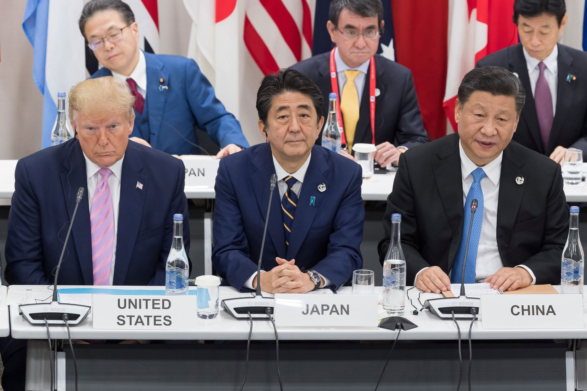 US President Donald Trump (L) sits with Japan's Prime Minister Shinzo Abe (C) and China's President Xi Jinping as they attend a meeting on the digital economy at the G20 Summit in Osaka on June 28, 2019.