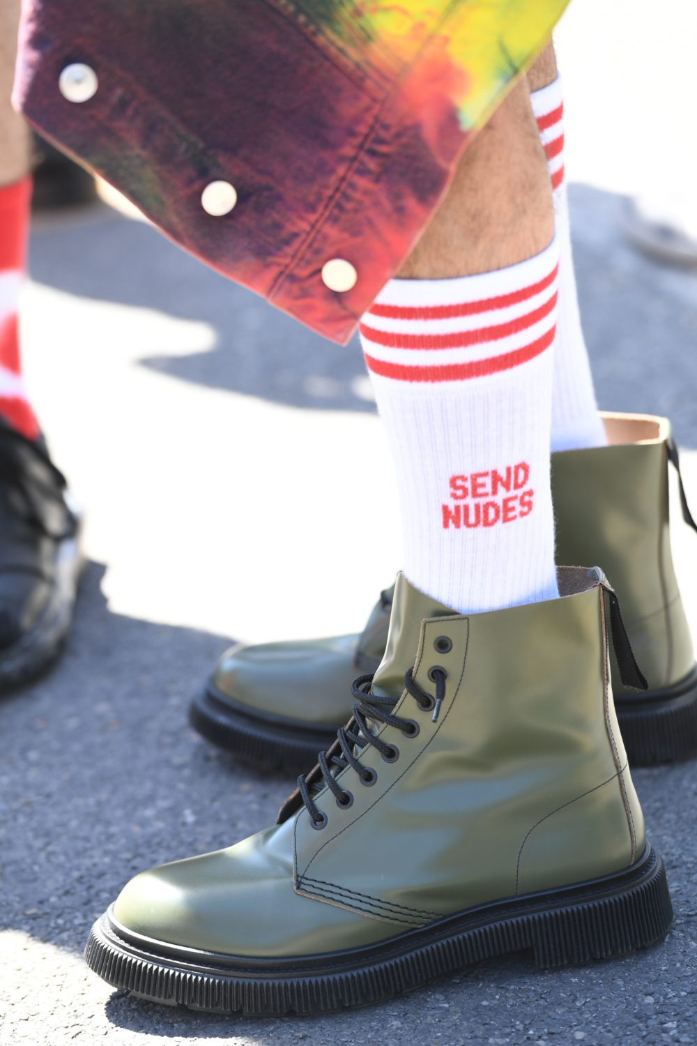 Men on the scene for Pitti Immagine Uomo trotted out a range of shoe styles bringing fashion to the street. This gentleman paired suggestive socks with olive combat-style boots.