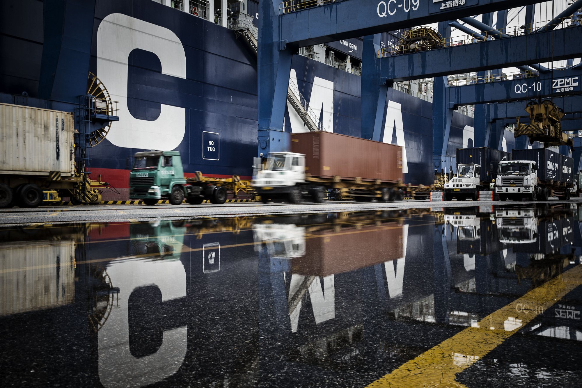 Trucks are reflected in a puddle as they wait in line to unload their containers onto CMA CGM SA's Benjamin Franklin container ship docked at the Guangzhou Nansha Container Port in Guangzhou, China.