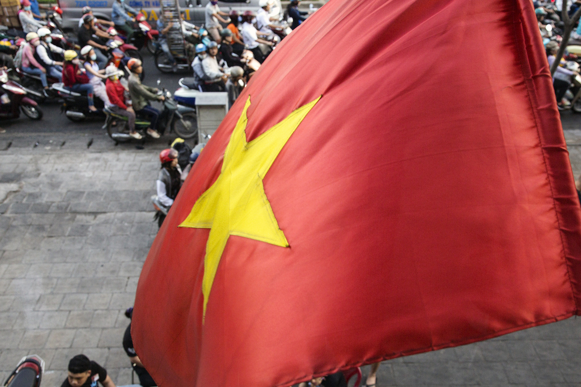 A Vietnamese national flag flies as motorcyclists wait at a traffic signal in Ho Chi Minh City, Vietnam, on Friday, Jan. 12, 2018.