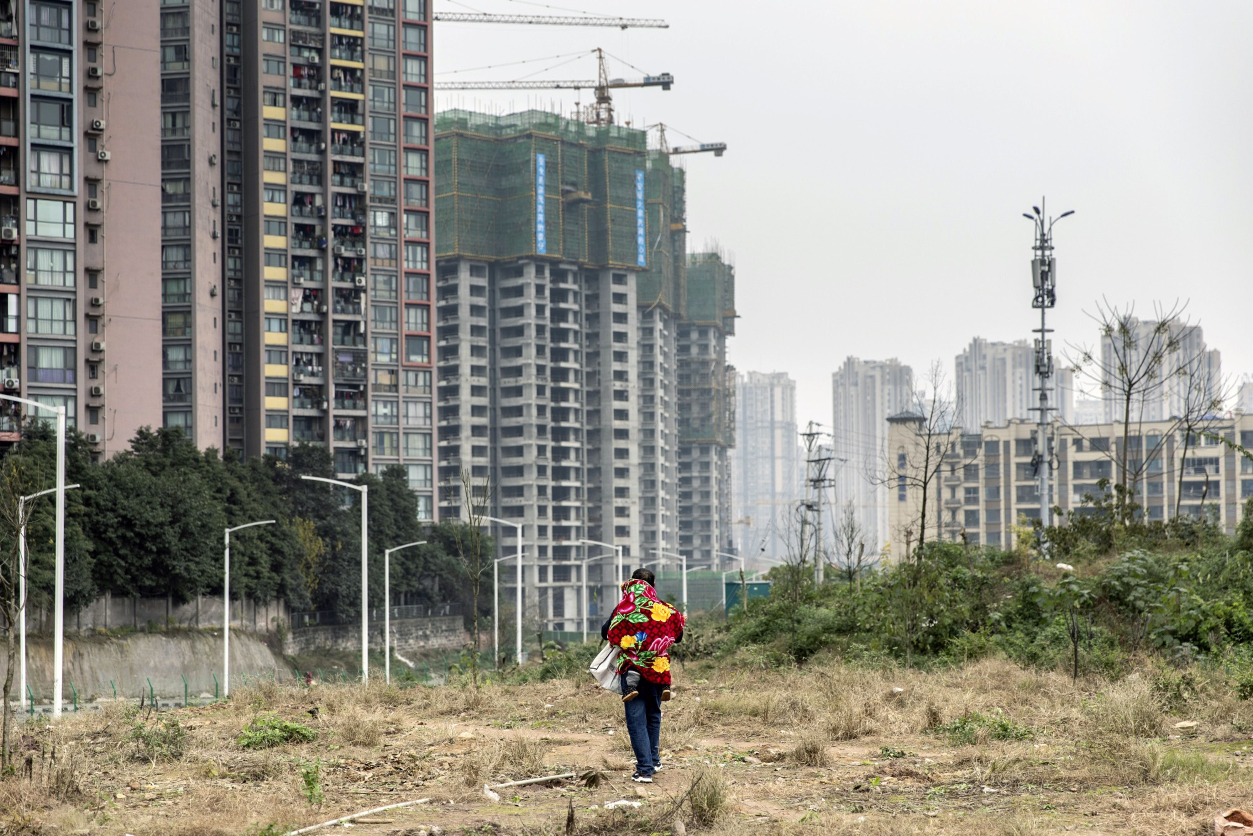 A man carrying a child on his back walks on a field near new housing developments on the outskirts of Chongqing, China,