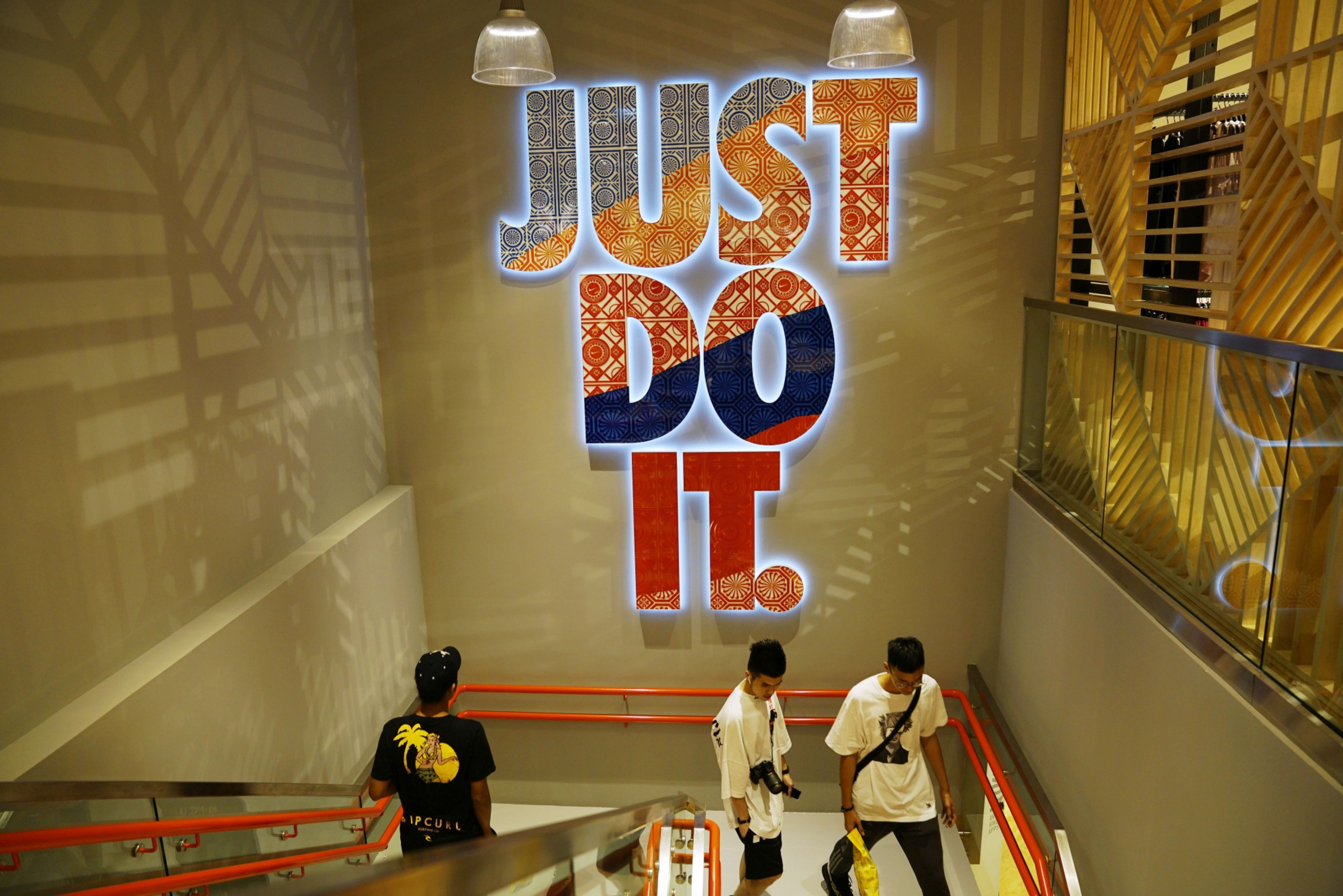 Shoppers walk down the stairs in a Nike store in Jewel Changi Airport in Singapore, on Thursday, April 11, 2019.