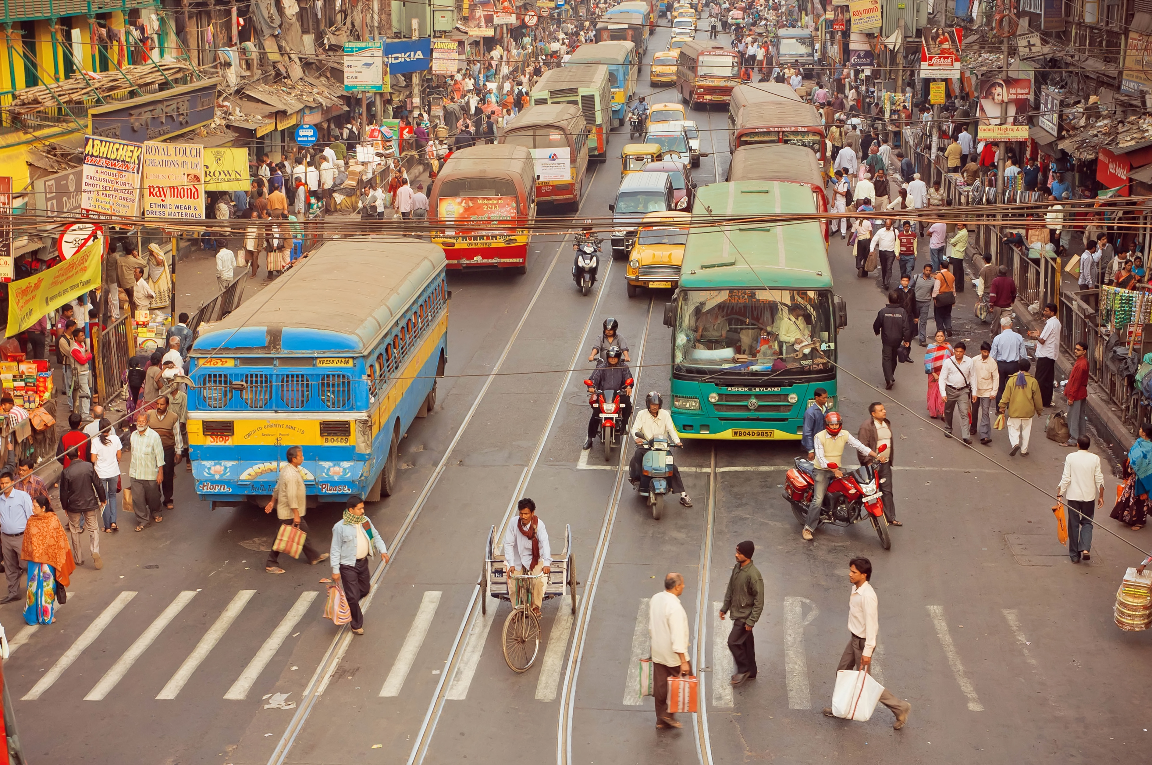 Crossroad of busy modern city in Asia with cars, bikes, walking people and buses on January 20, 2016 in Calcutta.