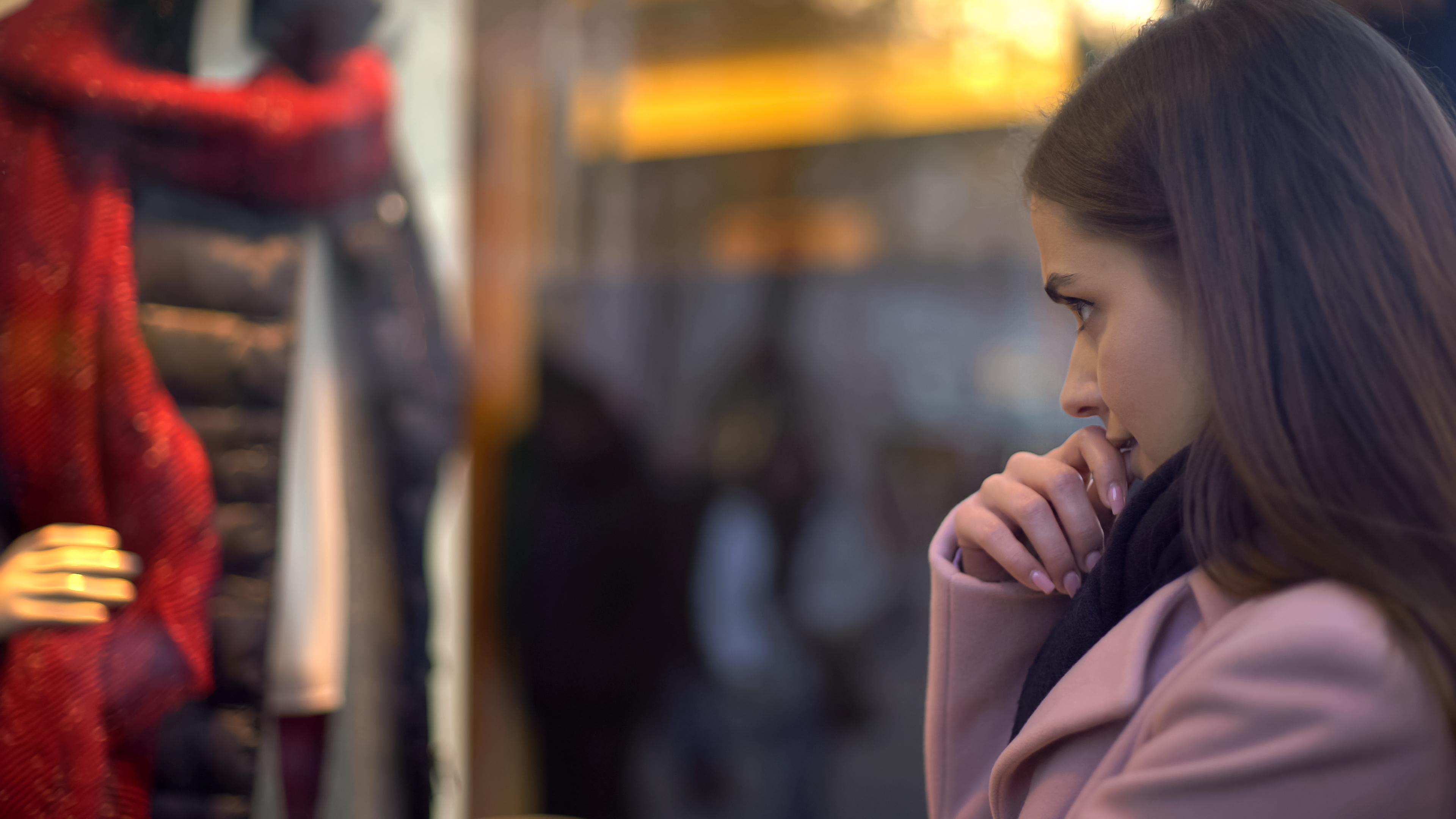 Beautiful lady looking at clothing in shop window, having not enough money